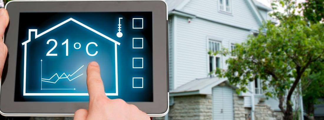 Mano manejando una Tablet regulando una temperatura y una casa de fondo.