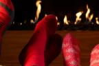 Pies con calcetines frente a una chimenea encendida