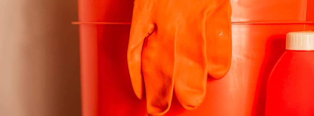 Cubo naranja con guante de látex y bote de lejía