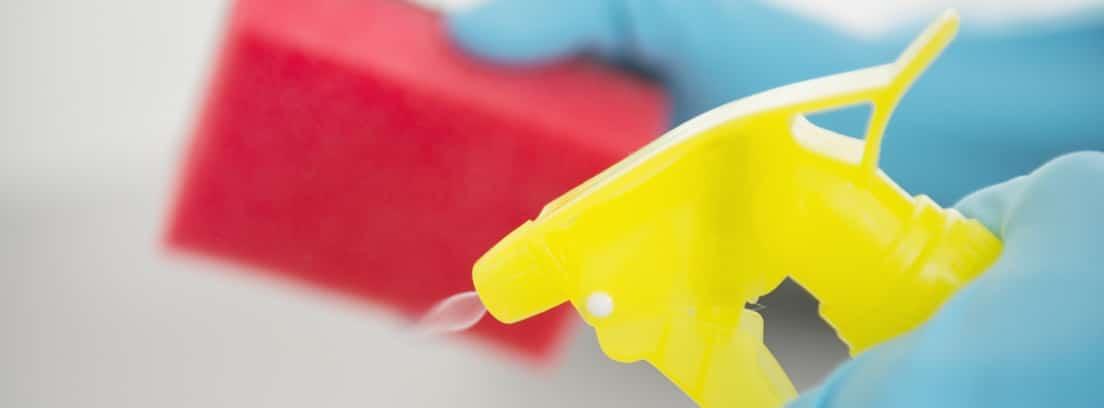 Manos con guantes aplicando un producto de limpieza sobre un estropajo