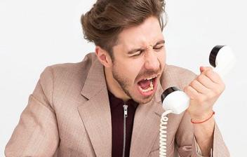 Hombre gritando a un teléfono para dar de baja los suministros