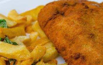 Plato con cachopo, pimientos de piquillo y patatas fritas