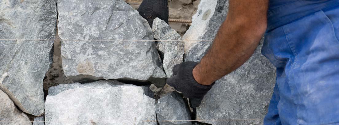 Hombre construyendo una pared de piedra natural