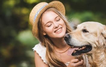 chica con sombrero acaricia a un perro de raza Golden retriever