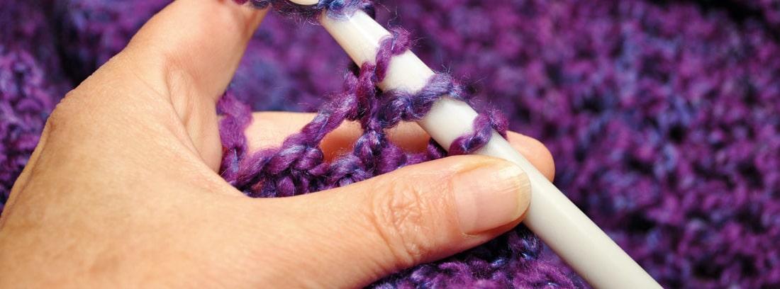 Manos realizando crochet con una lana morada