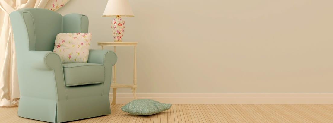 Sillón azul junto a una mesita con una lámpara y unas cortinas con abrazaderas
