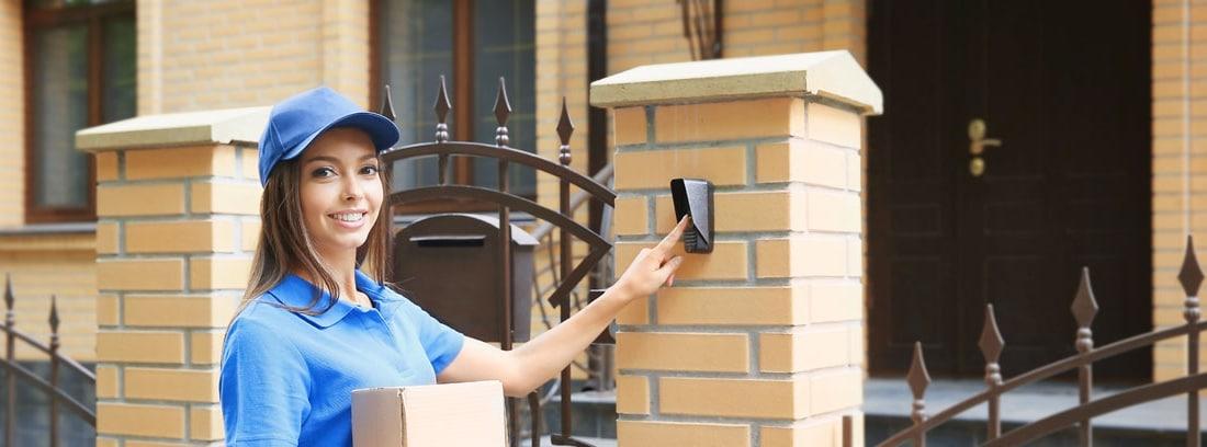 Mujer con gorra azul y paquetes en la mano llamando al timbre de una casa