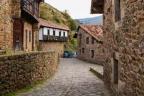 Calle empedrada flanqueada por casas de piedra