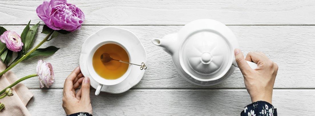 Vista cenital de unas manos sobre una mesa con una tetera, una taza de té y unas flores.