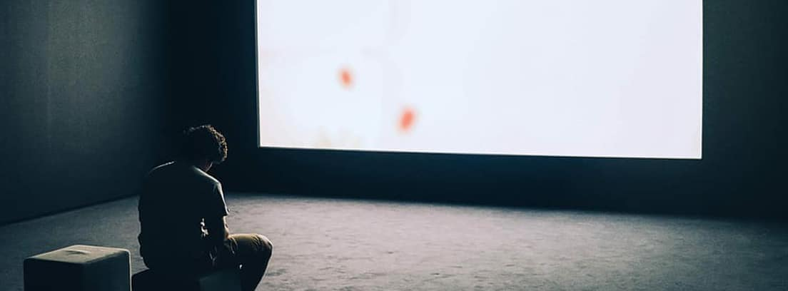 Hombre cabizbajo sentado frente a una pantalla de proyección