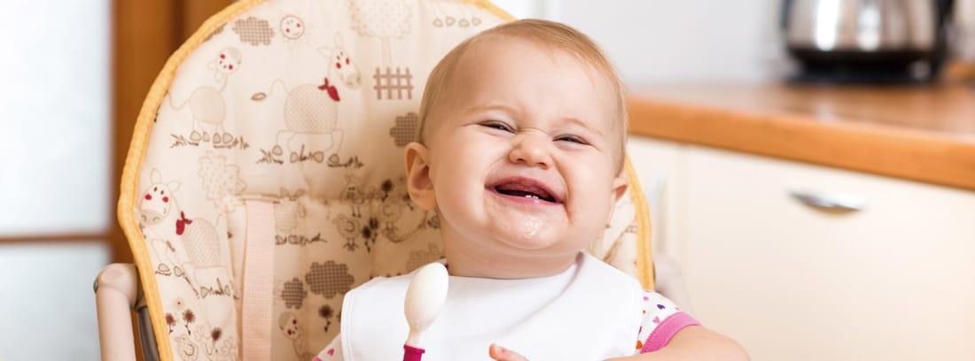 Bebé sonriente sentado en una trona con una cuchara y un plato