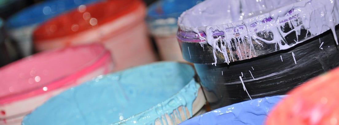 Botes de pintura de distintos colores abiertos