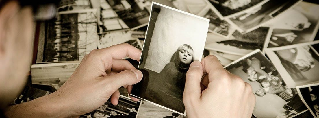 Hombre sosteniendo fotos antiguas en sus manos.