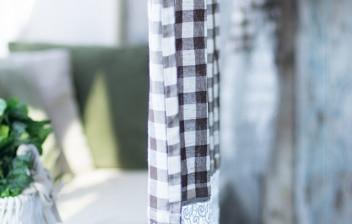 Planta sobre el alfeizar de una ventana, cortina rústica y silla
