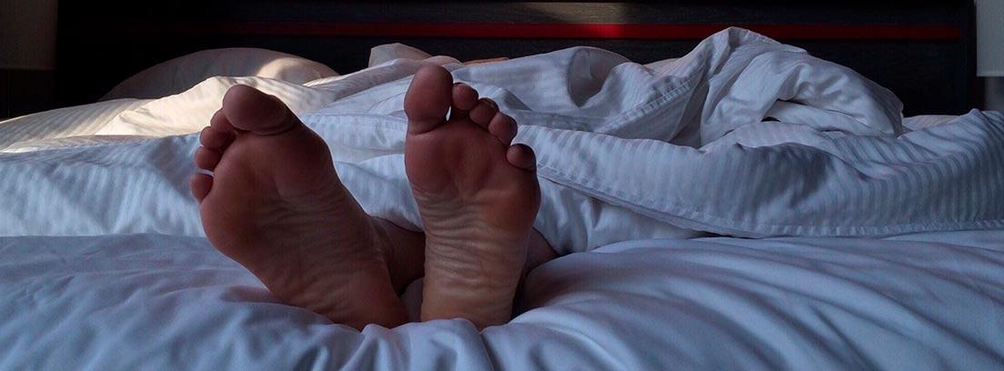 Pies asomando debajo de una sábana