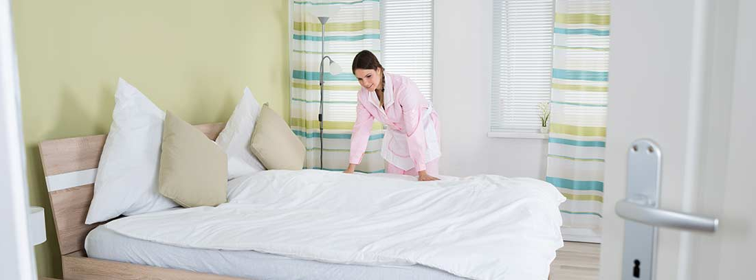 Mujer poniendo la funda nórdica en la cama