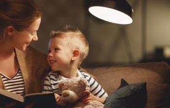Madre y bebé en brazos con un libro entre las manos