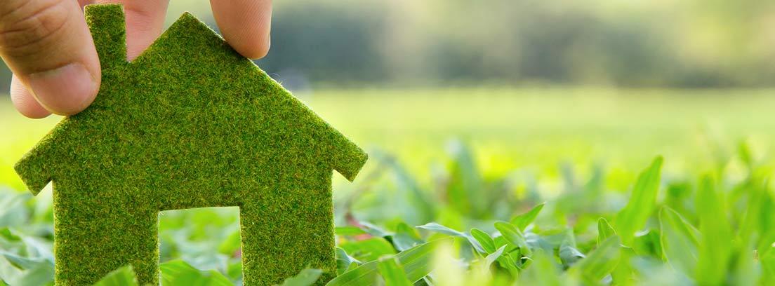 Mano poniendo una silueta de una casa verde en el césped