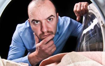 Hombre mirando el interior de una lavadora