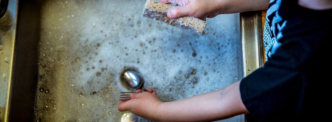 Niño fregando unas cucharas a mano