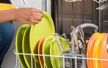 Mano colocando platos de colores en el lavavajillas