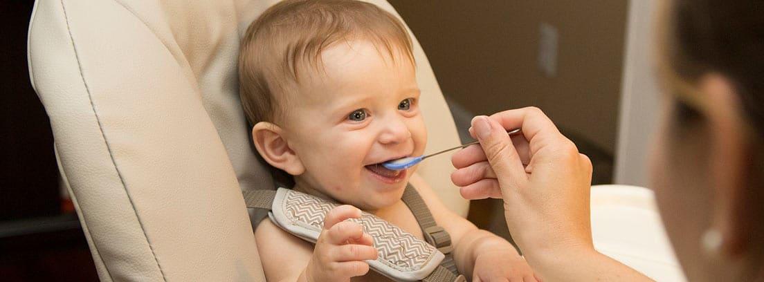 Bebé sonriente comiendo puré