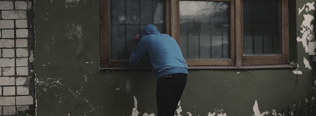 Hombre encapuchado mirando por la ventana en el interior de un inmueble