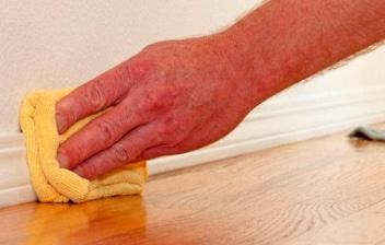 mano limpiando rodapiés con una esponja