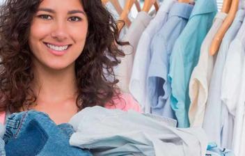 Mujer sonriente con una caja llena de ropa en la que pone donación