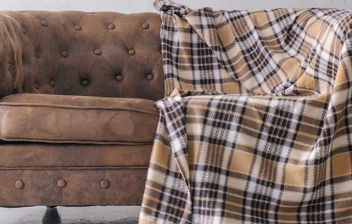Sofá Chesterfield marrón con una manta de estampado de cuadros