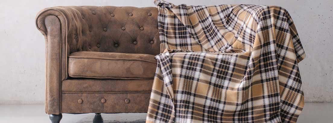Sofá Chesterfield marrón con una manta de estampado de cuadros