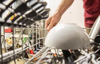 Hombre poniendo platos en un lavavajillas