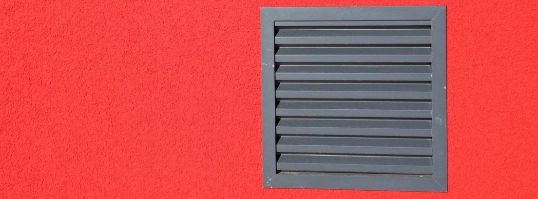 Rejilla de ventilación en una pared roja