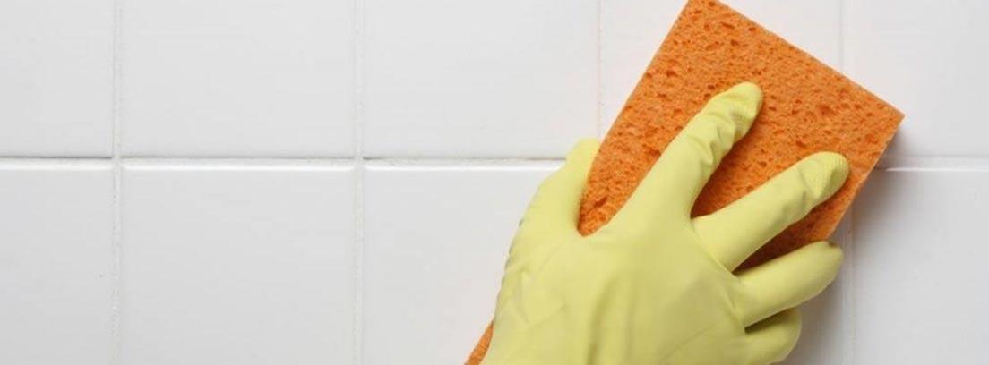 Mano con esponja limpiando unos azulejos blancos