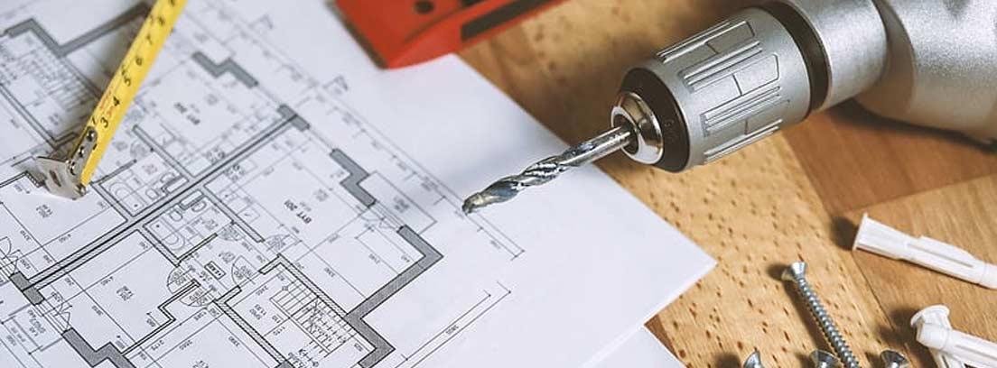 Planos de una casa, taladro, nivel, metro, tronillos y tacos