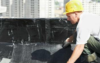Hombre colocando tela asfáltica sobre un tejado