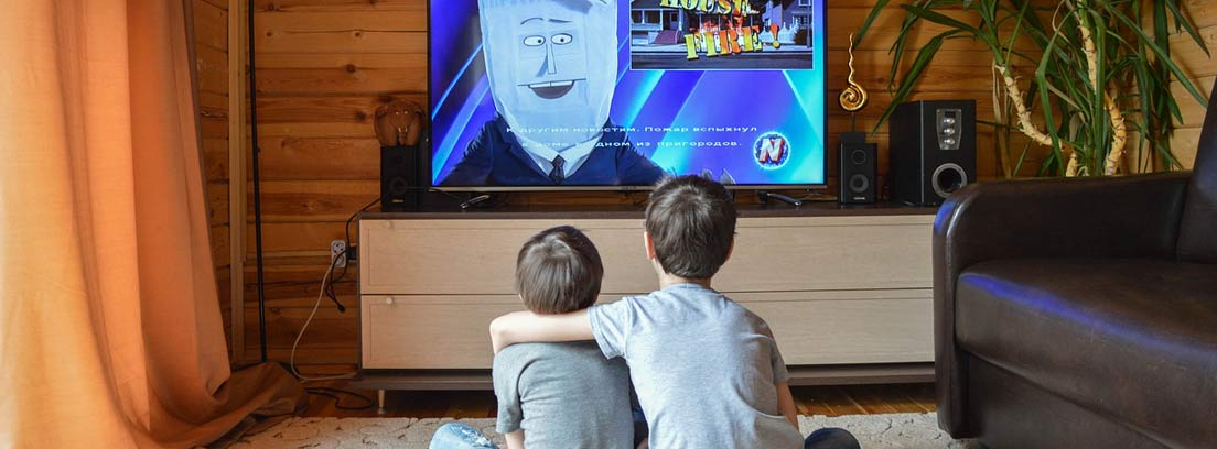 Dos niños abrazados sentados en el suelo frente a una televisión