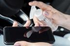 Manos usando un gel desinfectante para limpiar un móvil