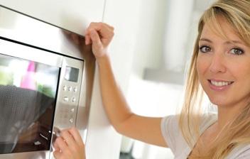 Mujer junto a un microondas encastrado