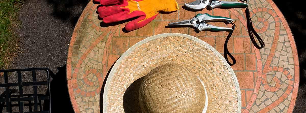 Vista cenital de una mesa con unas tijeras de podar y un sombrero de paja