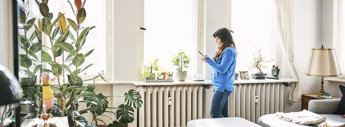 Mujer de pie mirando al móvil delante de unos ventanales y unos radiadores
