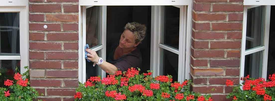 Mujer limpiando una ventana por fuera