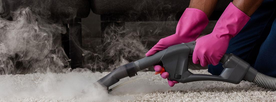 Persona con guantes utilizando un limpiador a vapor sobre una alfombra
