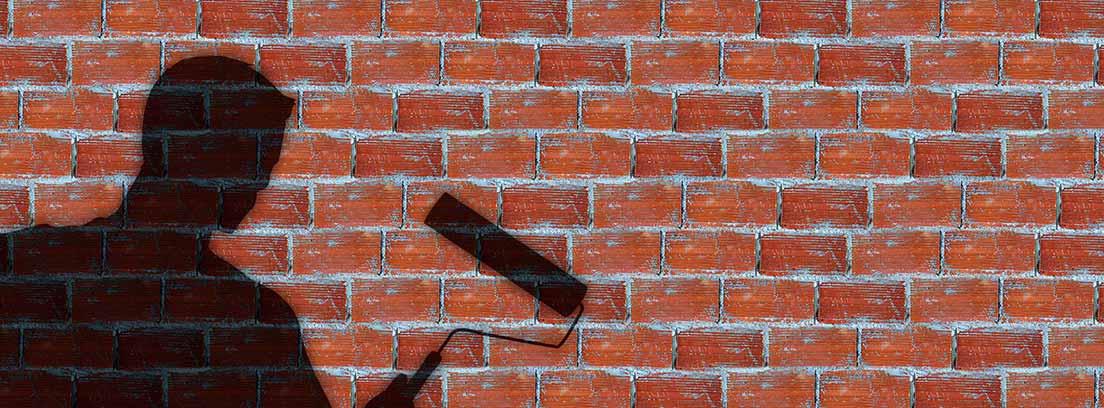Sombra de un hombre sujetando un rodillo sobre una pared de ladrillo