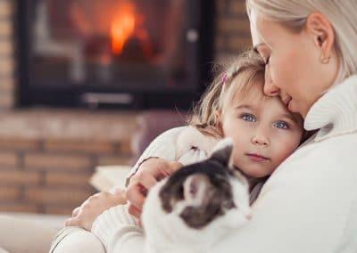 Mujer y niña con un gato sentadas junto a una chimenea con revestimiento de ladrillo