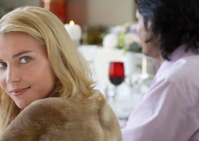 Mujer mirando a cámara sentada en una mesa con otros comensales