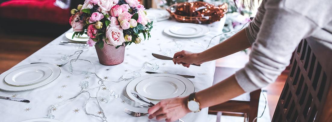 Mujer colocando unos cubiertos en una mesa