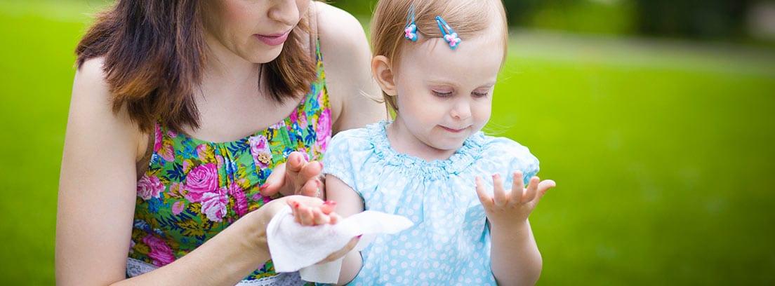Mujer con una niña limpiándose las manos con toallitas húmedas