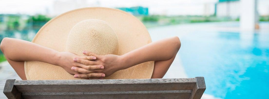 Mujer con pamela sentada junto a una piscina