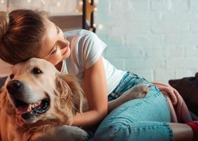 Chica joven abrazada a su perro de raza Golden Retriver